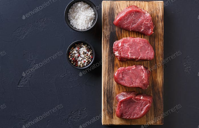 Raw beef filet mignon steaks with spices on wooden board at blac