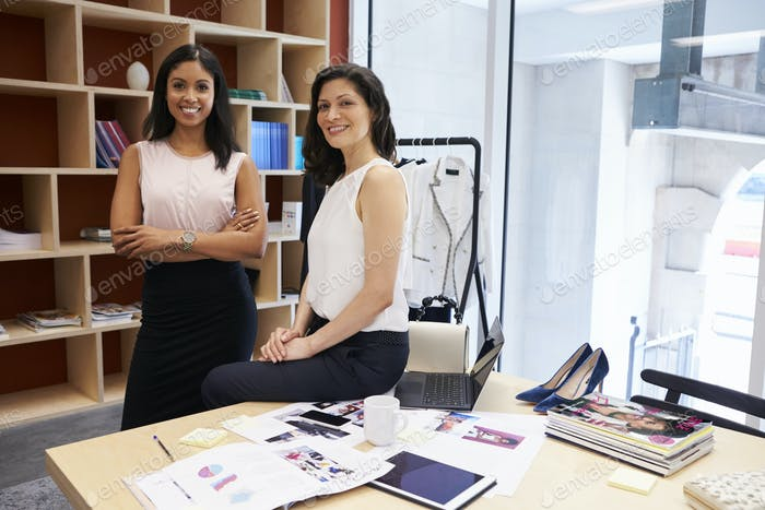 Two female creatives in an office smiling to camera