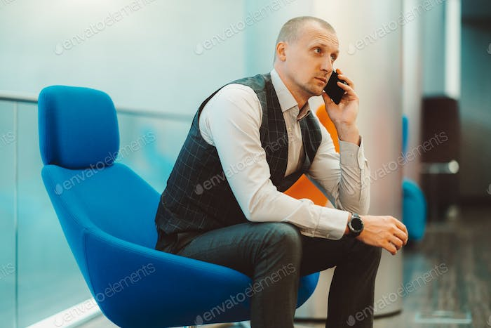 Businessman sitting in blue armchair