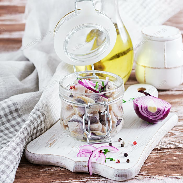 Marinated herring in jar with onions. Scandinavian food.