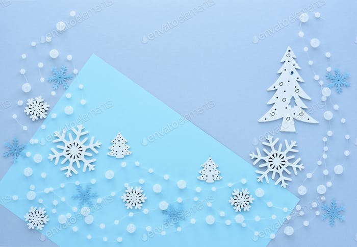 Snowflakes, spruce and beads on pastel blue background.