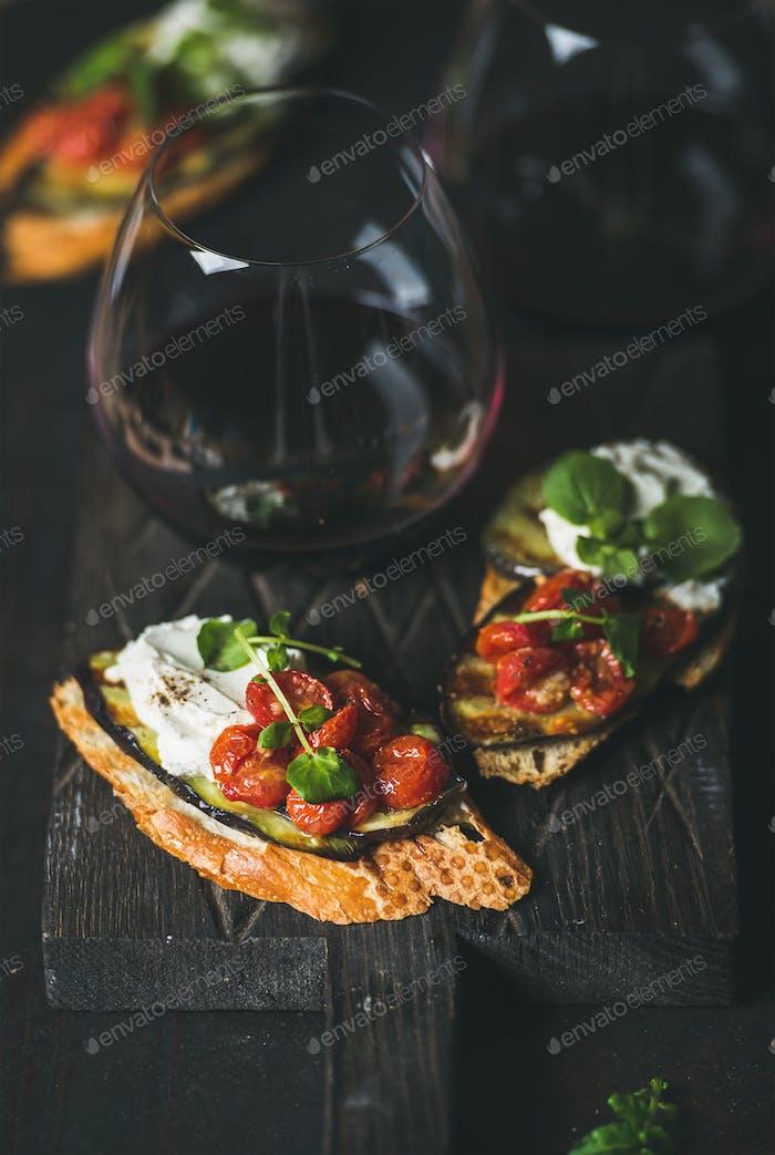 Brushetta with eggplant, tomatoes, garlic, cream-cheese, arugula, glass of wine
