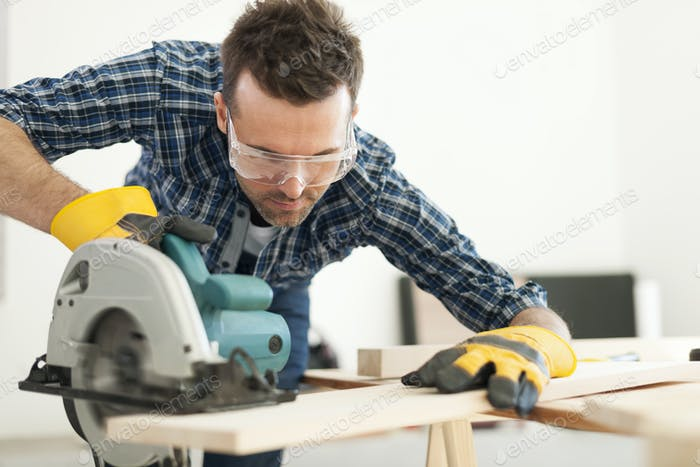Hard working carpenter cutting wooden plank