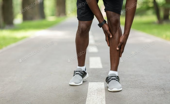 Black sportsman touching his aching leg while jogging outdoors