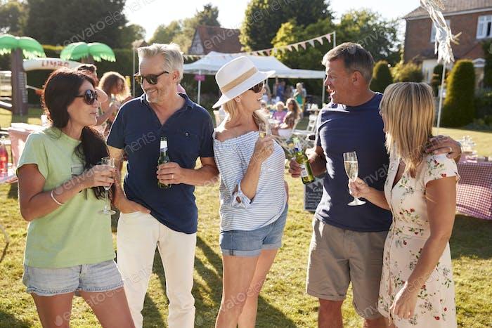 Mature Friends Enjoying Drinks At Summer Garden Fete