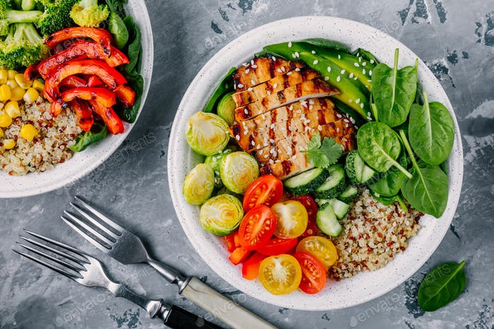 Healthy buddha bowl grilled chicken, quinoa, spinach, avocado, brussels sprouts, tomatoes, cucumbers