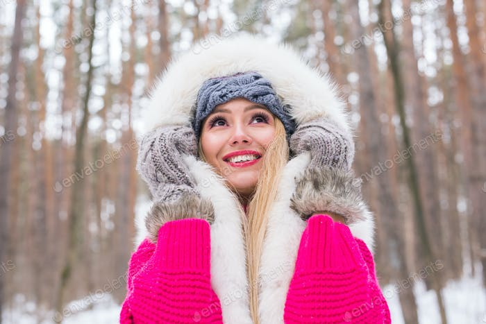 Fashion, beauty and people concept - Portrait of blond young woman in fur coat at winter background