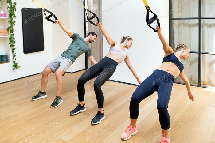 Drei Personen Training Power Pull mit Trx im Fitnessstudio