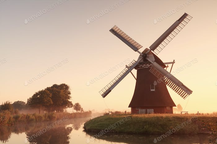 charming windmill by river at sunrise
