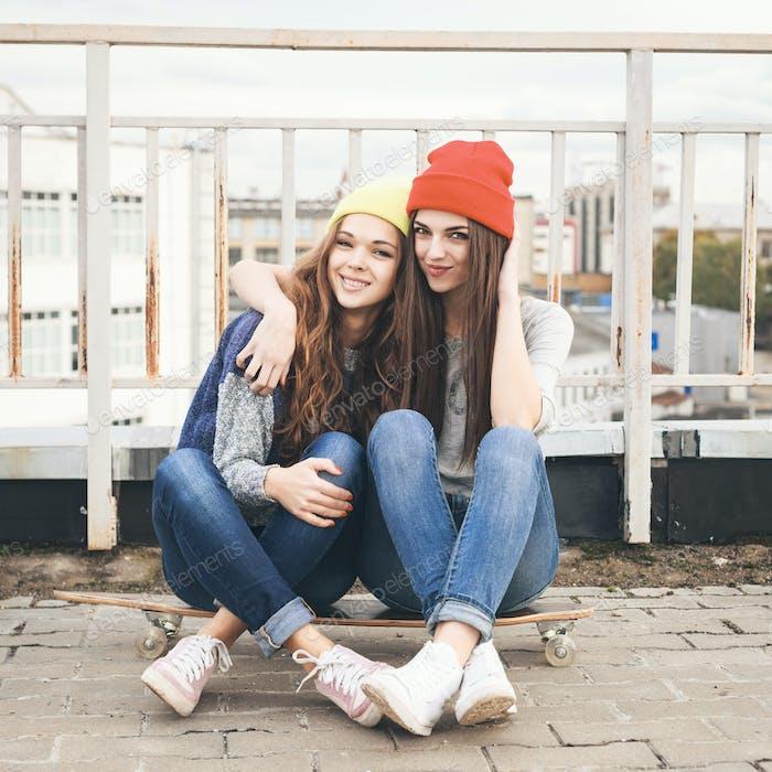 Two young  longboarding girl friends