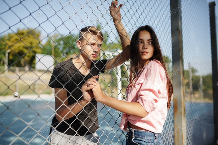Young beautiful girl and boy standing between mesh fence on basketball court
