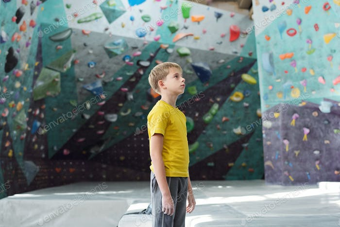 Sporty youngster in activewear standing in the middle of climbing room