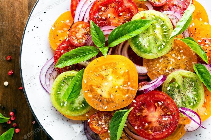 Tomato salad. Fresh vegetable salad with tomatoes, onion and basil