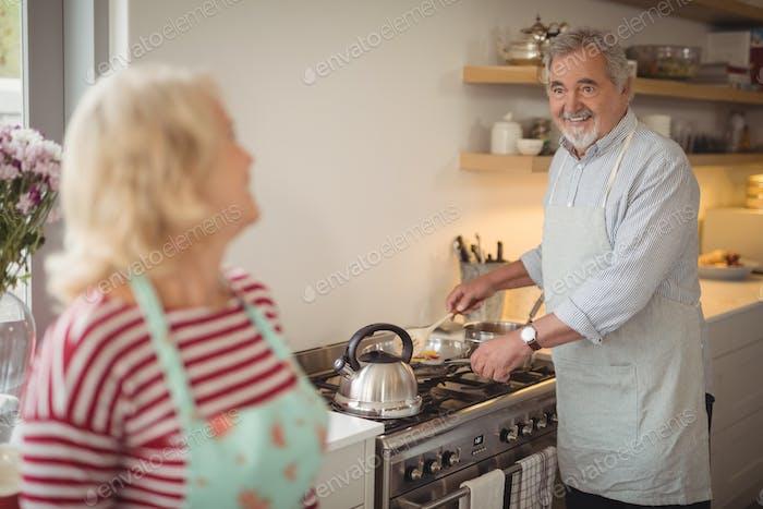 Senior couple preparing food while interacting in kitchen