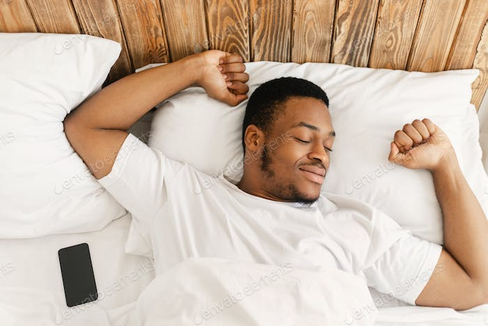 Rested African Guy Waking Stretching Hands Awakening In Cozy Bedroom