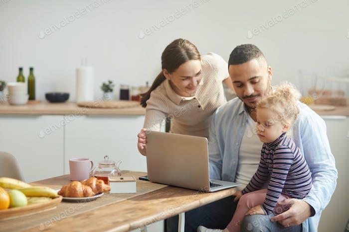 Moderne Familie mit Laptop mit niedlichen kleinen Tochter