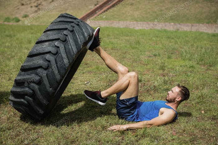 Fit man performing leg workout with tier during obstacle course