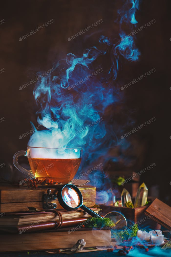 Hot cup of tea with a dense rising steam, magnifying glass, books and dried plants