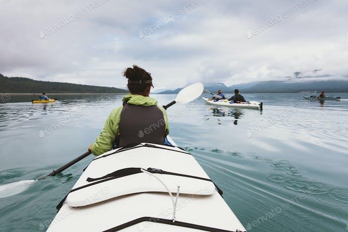 Gruppe von Seekajakern, die unberührte Gewässer einer Bucht an der Küste von Alaska paddeln.