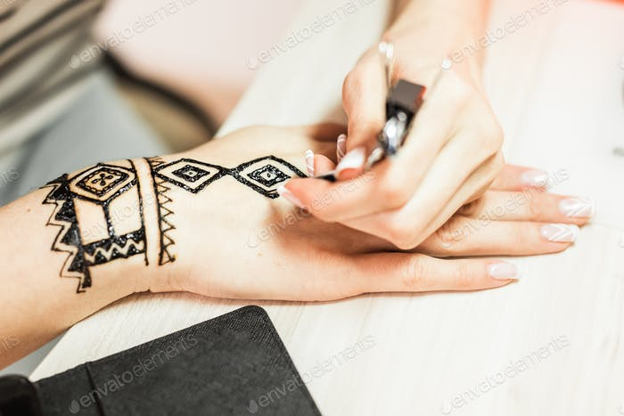 young woman mehendi artist painting henna on the hand