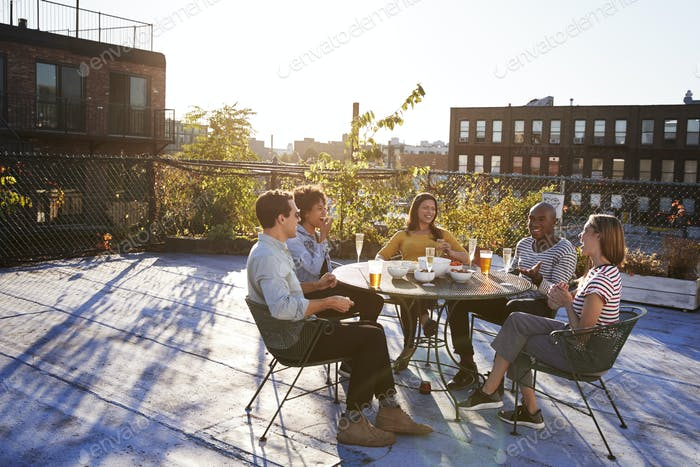 Five friends sit talking at a table on a New York rooftop