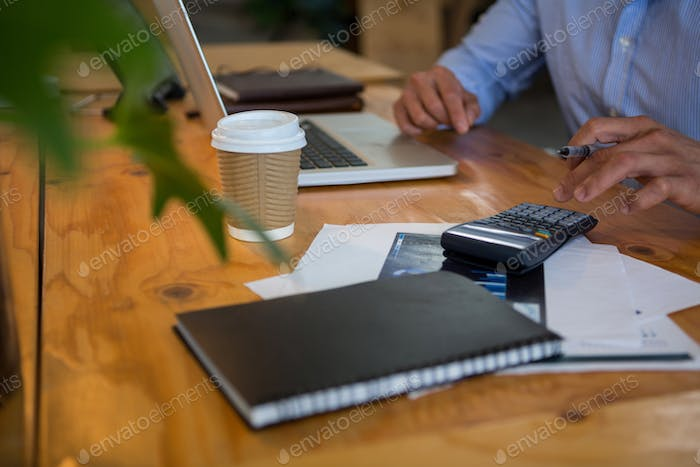 Business executive using calculator in office