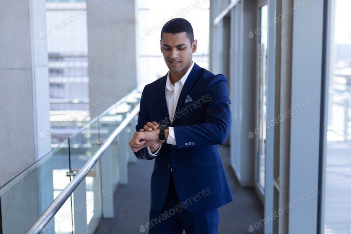 Front view of handsome young mixed-race businessman using smartwatch standing in modern office