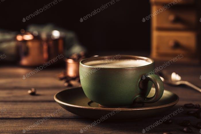 Grüne Tasse Kaffee mit Kaffeemühle