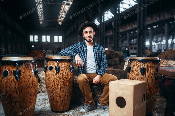 Male drummer pose against african wooden drum
