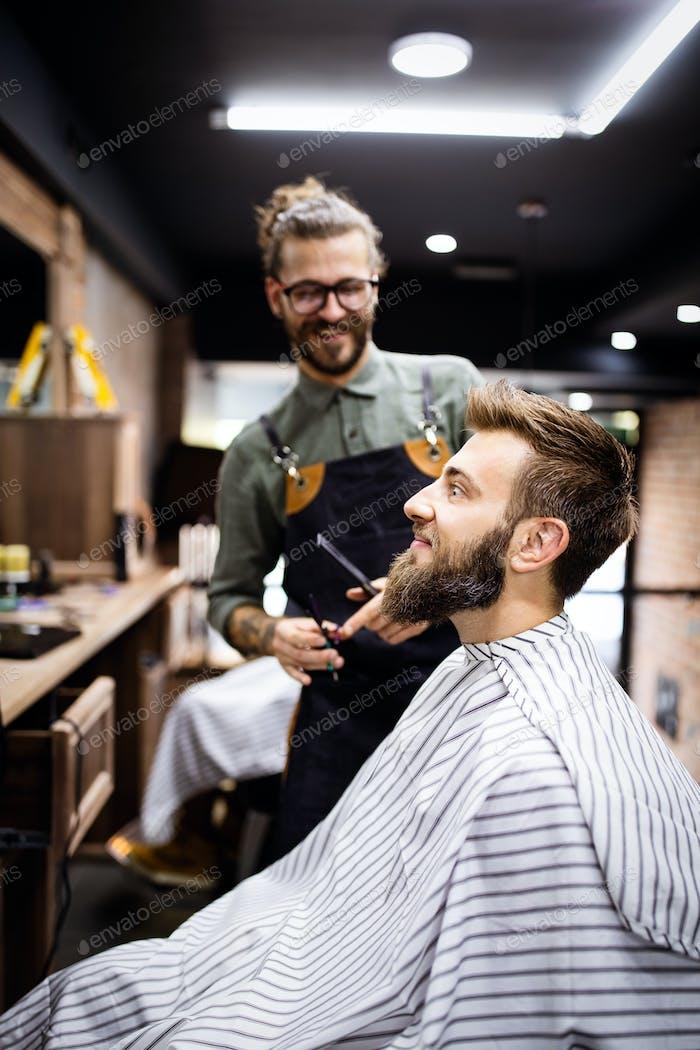 Портрет счастливого юного парикмахера с клиентом в парикмахерской и улыбаясь
