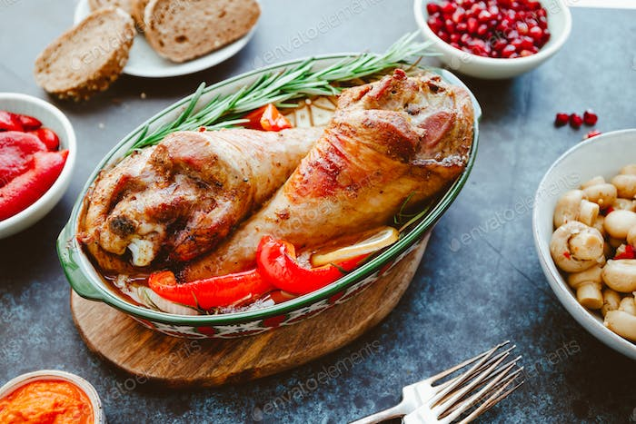 Festive dish for Thanksgiving, roasted turkey legs with vegetables on a table with appetizers