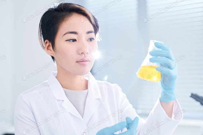 Young Asian chemist analyzing fluid