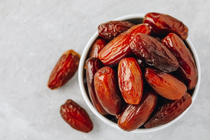 Dried dates in white bowl on grey background