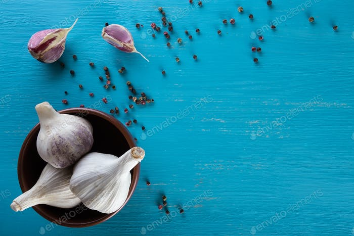 Garlic in plate and pepper on blue wooden table