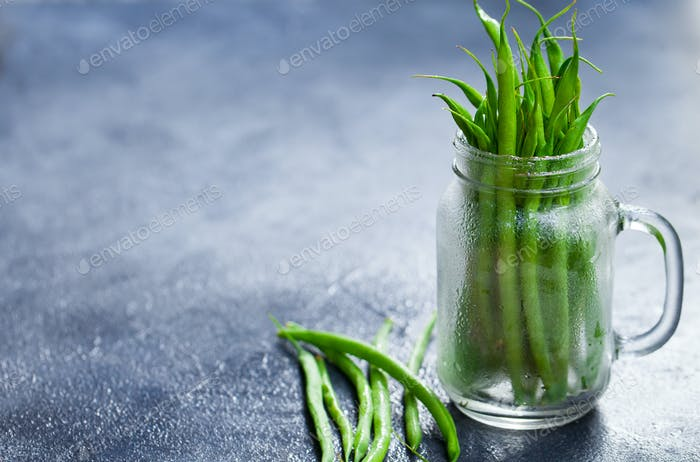 Green Beans in Glass Jar on Grey Stone Background. Copy Space.