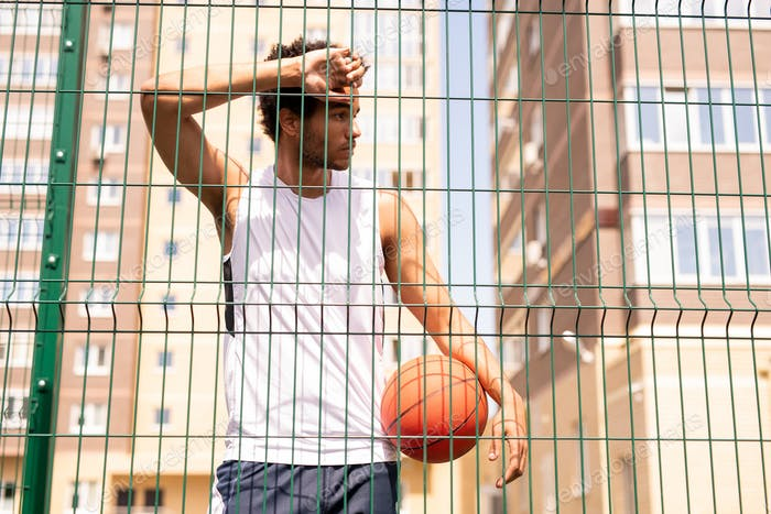 Adolescent basketball player in activewear leaning against fence of the court