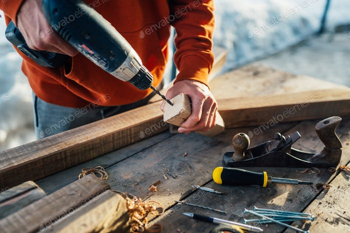 a worker drills a hole in  wooden bar with   drill
