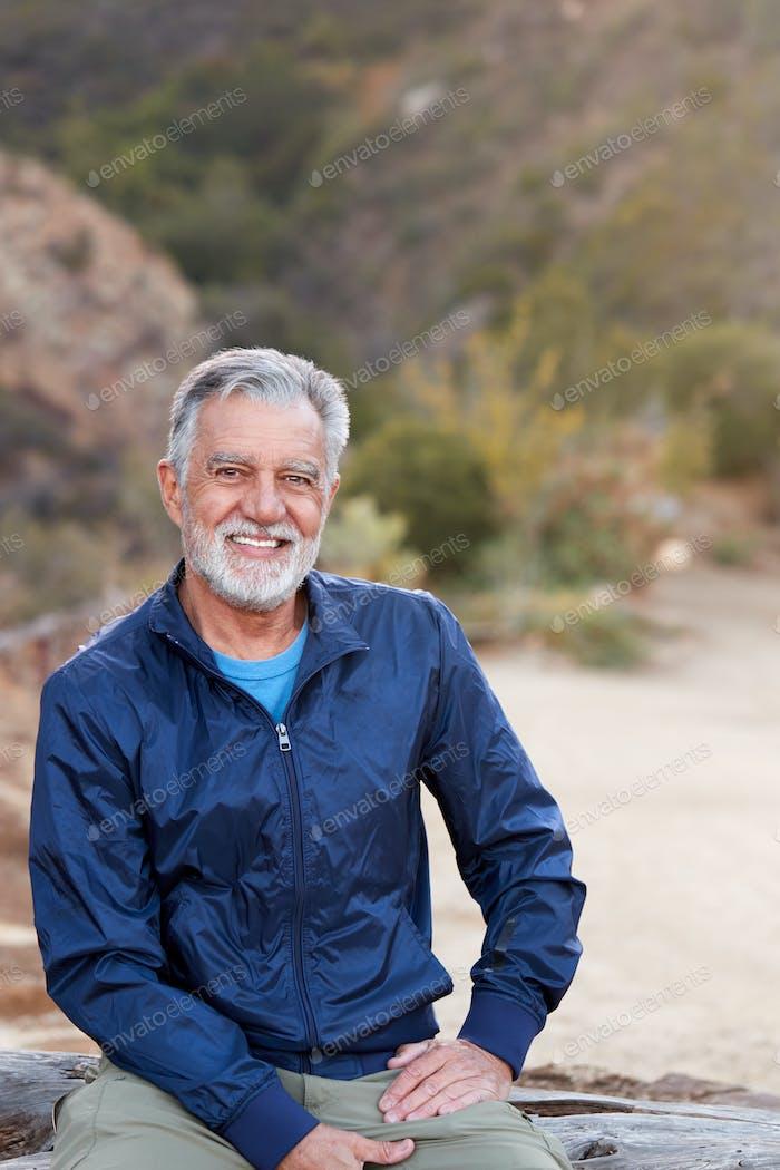 Portrait Of Smiling Hispanic Senior Man Outdoors In Countryside