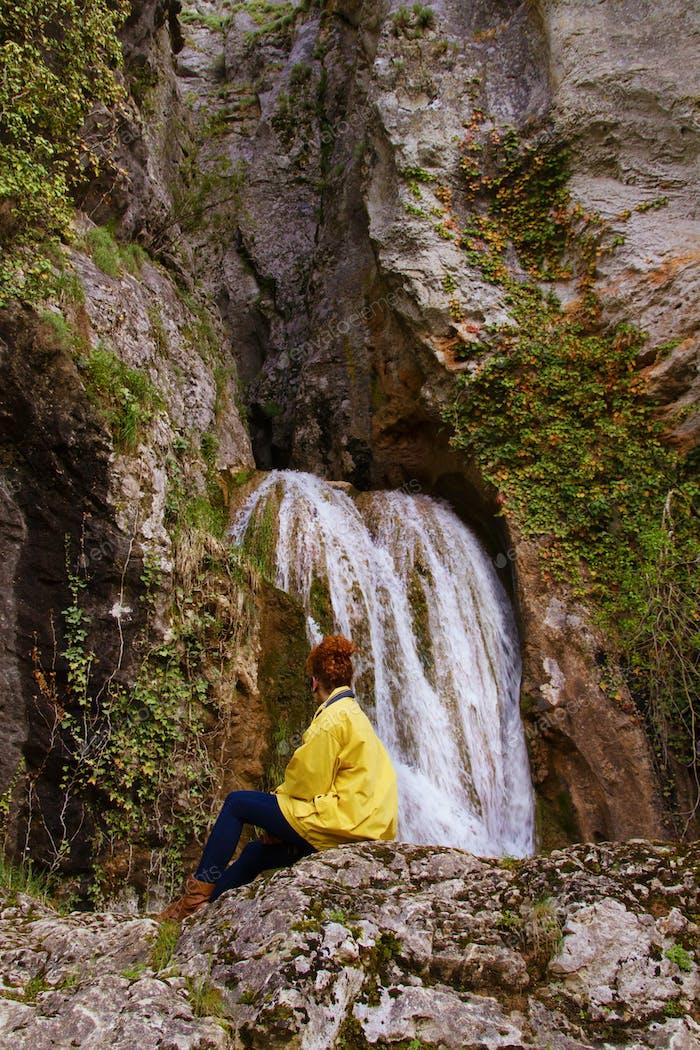 Junge Frau allein vor einem Wasserfall