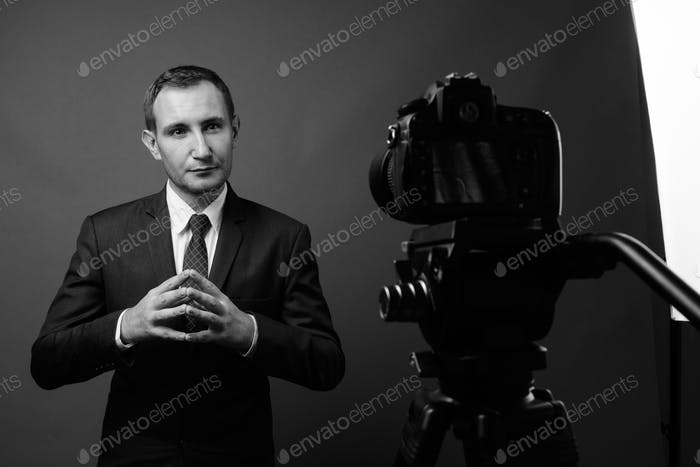 Portrait of businessman vlogging with camera against gray background