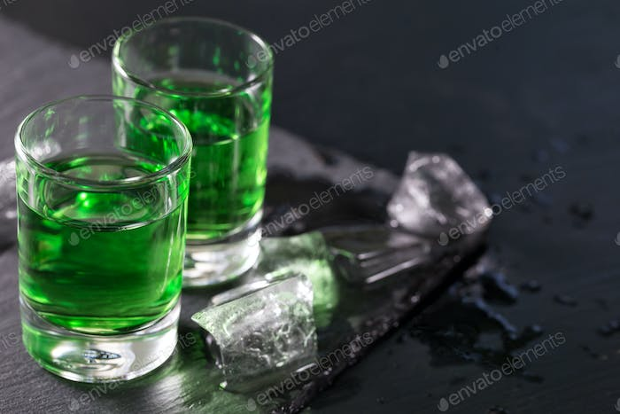 Two glasses of absinthe and melted ice cubes