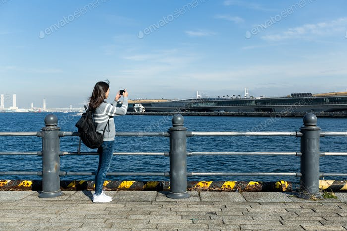 Woman take photo in Yokohama harbor