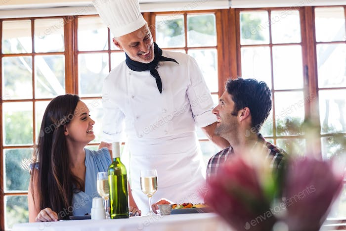 Male chef talking to couple at restaurant