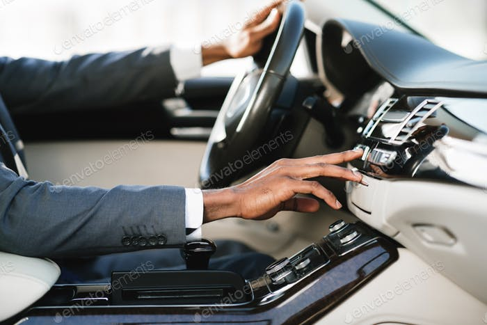 Afro businessman driving car and touching dashboard