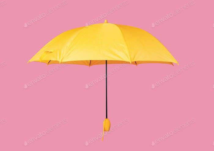 Opened yellow umbrella isolated on pink background