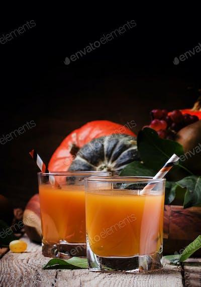 Pumpkin juice on vintage wooden background, selective focus