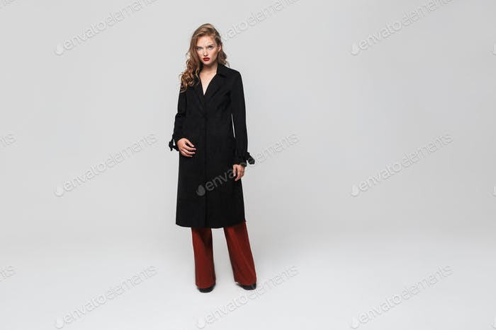 Young beautiful woman with wavy hair in black coat and red trousers thoughtfully looking in camera