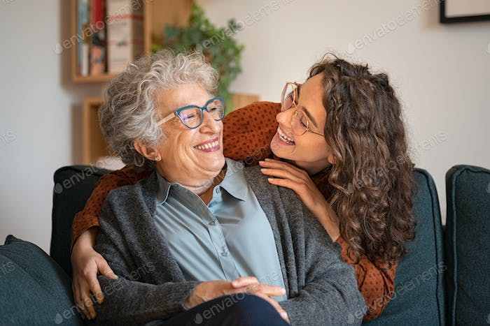 Grandmother and granddaughter laughing and embracing at home