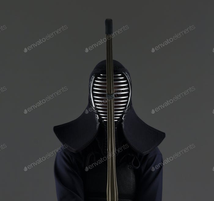 male in tradition kendo armor with bamboo sword .