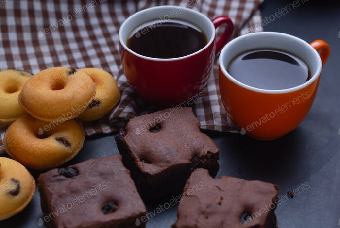 Cups of black coffee with brownies and mini donuts